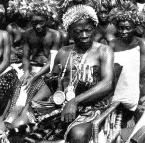 Chef tribal Karume On remarquera sa plaque ronde en sautoir attribuée par l'Administration coloniale. Il est le seul à pouvoir être assis, à porter une coiffe de chef et à manipuler un chasse-mouche en guise de signe d'autorité. Il porte une parure en porte de léopard et est entouré de ses femmes.