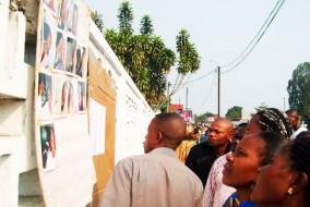 Les gens regardent des photos de victimes blessées devant l'hôpital de Loandjili à Pointe-Noire le 22 Juin 2010. - Photo: AFP.