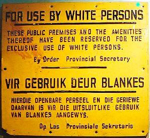 Ecrit en anglais (haut) et allemand (bas): Les lieux publics et les équipements de sont réservés à l'usage exclusif des personnes  blanches
