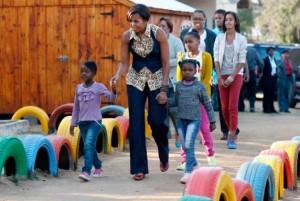 Michelle Obama marche avec les enfants lors de sa visite du Centre communautaire Emthonjeni situé à Zandspruit en Afrique du Sud, mardi, le 21 juin 2011