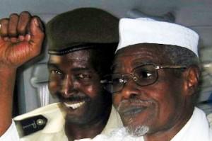 L'ancien président tchadien Hissène Habré lève le poing en signe de victoire alors qu'il quitte un tribunal de Dakar, escorté par un policier sénégalais le 18 novembre 2005