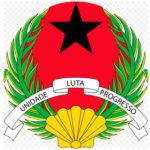 """Les armoiries de la Guinée-Bissau, comme le drapeau national, furent adoptées en 1973. Elles montrent les Couleurs panafricaines et l'étoile noire africaine. Dans la partie inférieure, on peut voir un coquillage doré qui représente les îles du Cap-Vert. Sur une ceinture d'argent entre deux branches de palmier, on peut lire la devise officielle du pays, en portugais: """"Unidade, Luta, Progresso"""" (Unité, Lutte, Progrès)."""