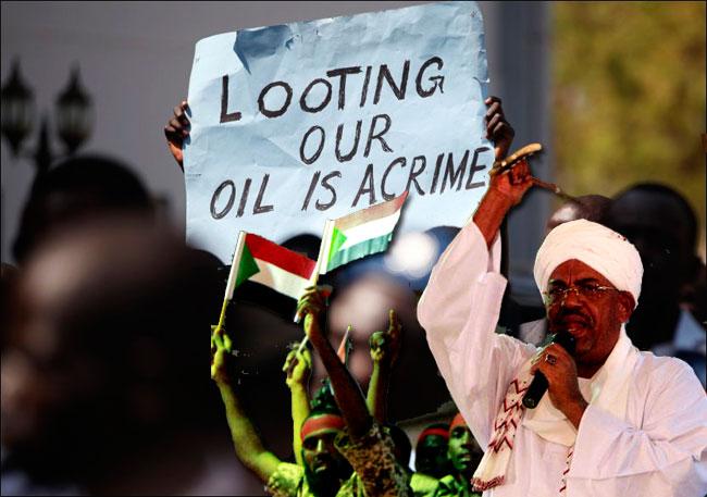 """Ecrit sur l'affiche: """"Piller notre pétrole est un crime"""", en réponse aux affirmations du gouvernement du Soudan du Sud qui affirmait, en janvier 2012, que le Soudan avait illégalement saisi 865 milions de dollars en pétrole brut"""