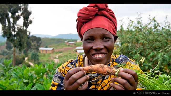 Dans une région du Rwanda, une femme montre fièrement une carotte qu'elle a cultivée dans ses jardins après avoir participé à un project financé par l'ACDI