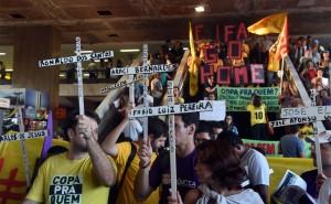 Les manifestants portant des croix avec les noms des personnes tuées lors de la rénovation des stades prennent part à une manifestation contre la prochaine Coupe du Monde 2014 au Brésil lors de la « Journée internationale de la Résistance Coupe du Monde » à São Paulo, Brésil, le 15 mai 2014. – Photo : Getty Images