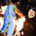 Des manifestants brûlent un album de collant de la Coupe du Monde de la FIFA Brésil 2014, lors d'une manifestation contre le prochain tournoi de la FIFA à Rio de Janeiro le 15 mai 2014. – Photo : Getty Images