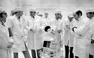 Au centre George R. Carruthers, principal chercheur de la caméra-spectrographe discute de l'instrument avec le commandant d'Apollo 16 John Young à droite, et directeur du programme Apollo Rocco Petrone, à gauche.
